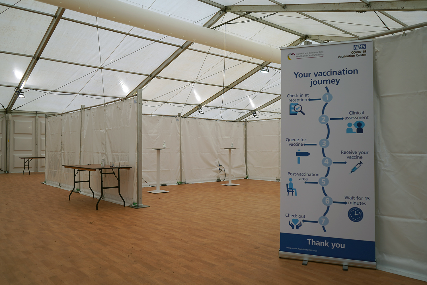 Entrance to Stithians Showground vaccination centre with sign showing vaccination journey